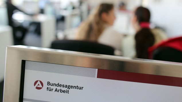 Blick in ein Jobcenter: im Vordergrund das Logo der Bundesagentur für Arbeit, im Hintergrund verschwommen zwei Frauen, die miteinander reden (dpa / picture alliance)