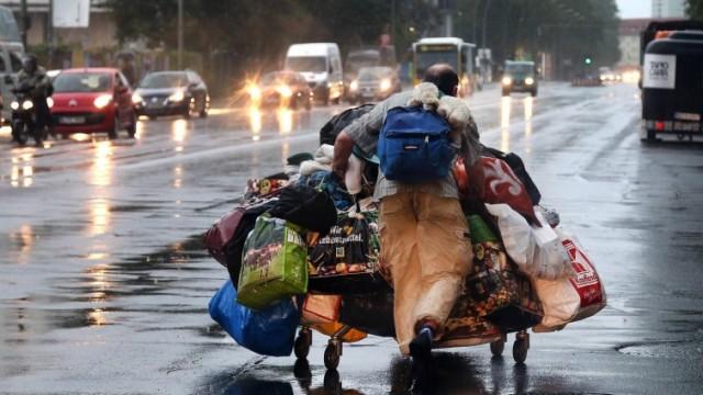 Ein Obdachloser versucht sein Hab und Gut vor dem Starkregen in Sicherheit zu bringen am 22.07.2017 inBerlin, Storkower Straße. (imago / Andreas Gora)